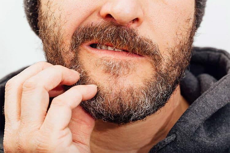 Uomo che si gratta per il prurito della barba